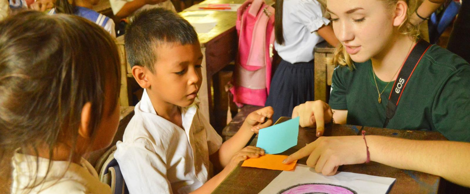 Childcare volunteer teaches a young boy different colours during school in Cambodia